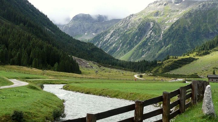 Foggy mountain view of a Bavarian valley in the Alps with a river or stream and a small road running into the forest.