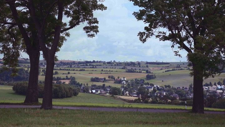 A European countryside view framed by large trees with grassy fields, hedgerows, roads and houses and trees on the horizon.
