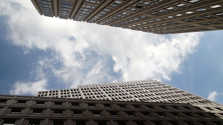 Wide Angle view of a cloudy sky between concrete high rise buildings or skyscrapers as found in Berlin or New York Manhattan.