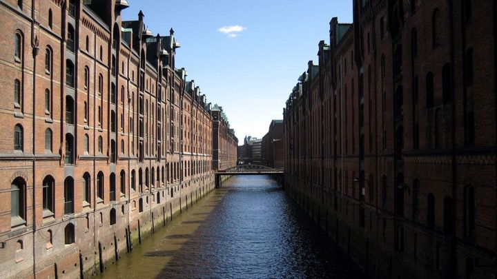 Canal in the city of Hamburgs urban harbor area Speicherstadt lined by old industrial and storage buildings.