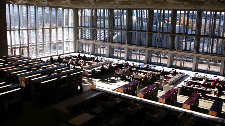 Students reading history or law books and studying in the glass fronted library reading room of Berlins State Library.