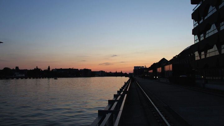 The golden light of sunset on a quiet river walkway at nightfall in Berlin with the skyline of the city in silhouette.