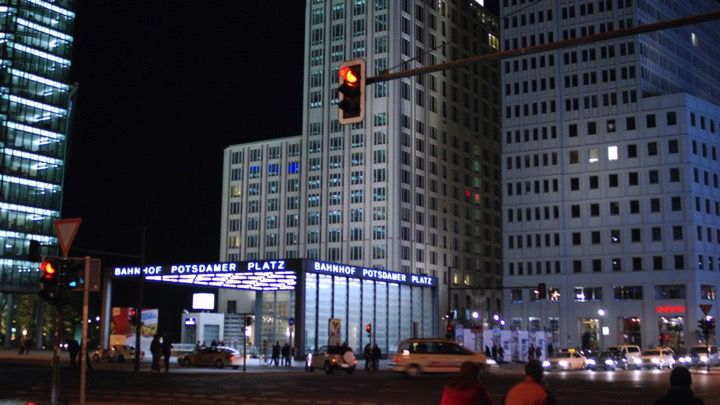 Busy traffic junction in Berlin at night with city lights and cabs surrounded by tall buildings in an upper class area.