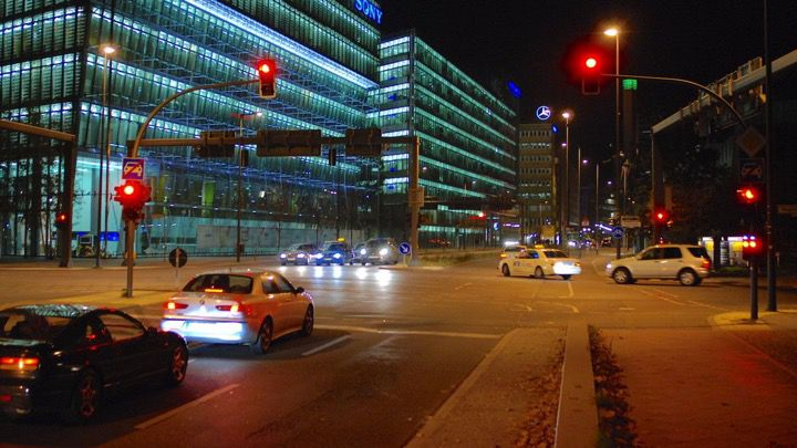 Large traffic light junction with street crossings in Berlin at night with factories and glass fronted buildings.