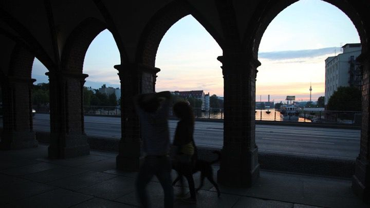 An underground view of the skyline from under a bridge at nightfall of the sunset over the river Spree in Berlin.