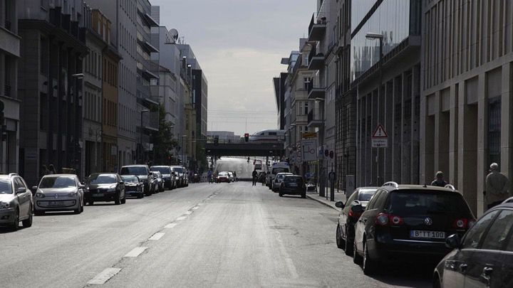 A lonely and wide street lined by parked cars and apartment buildings in Berlin